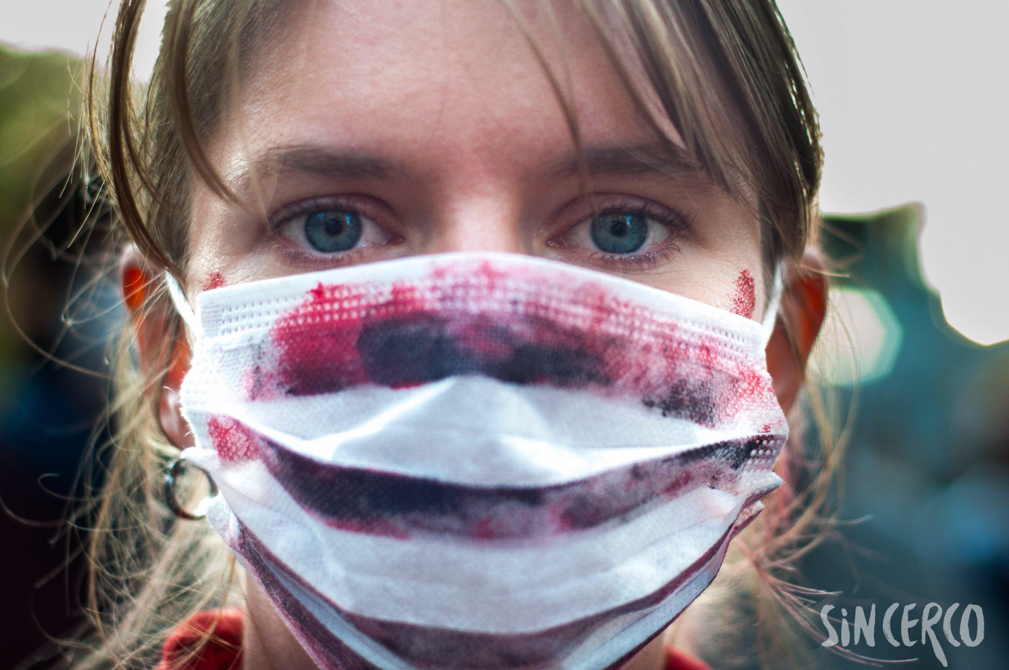Persona joven con barbijo manchado con sangre en La Marcha de los Barbijos
