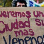"""Persona sosteniendo un cartel que dice """"Queremos una ciudad sin mas venenos"""""""