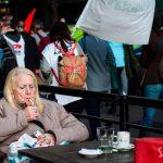 Persona sentada en un bar, enciendiendo un cigarrillo mientras a su lado pasa la Marcha de los Barbijos